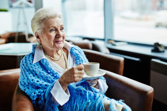 How to Stay Happy and Healthy This Winter - woman in shawl drinking coffee – The Goodman Group